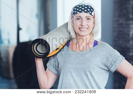 Stop Killing Time. Positive Minded Woman Grinning Broadly Into The Camera While Waiting For A Traini