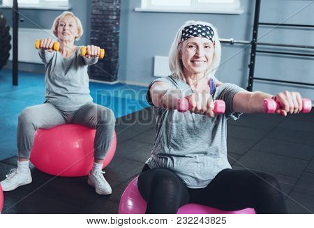No Regrets. Selective Focus On A Positive Minded Mature Lady Sitting On A Fitness Ball And Grinning