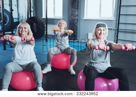 Train With Us. Selective Focus On Two Sporty Senior Women Sitting On Fitness Balls And Working With