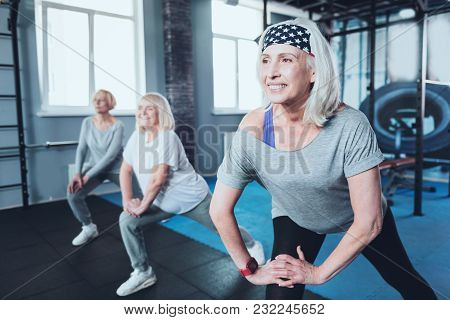 No Time For Worries. Selective Focus On A Smiling Retired Woman Doing Lunging Exercises While Standi