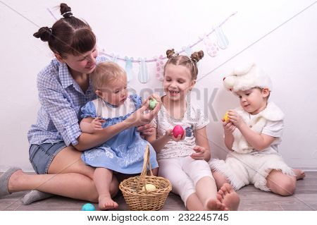 Family With The Family: Mom Gives Easter Eggs To Children. A Boy In A Rabbit Costume. Group Portrait