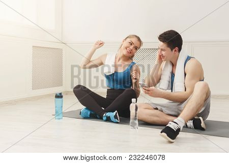 Fit Couple In Modern Gym Listening To Music On Smartphone. Sporty Man And Woman Having Rest After In
