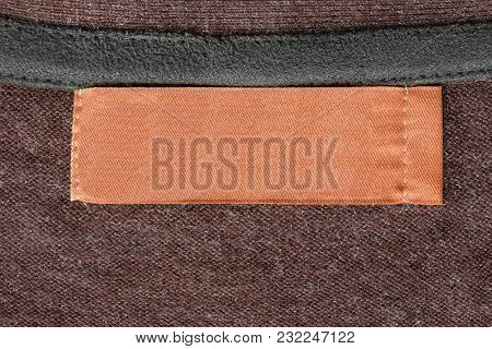 Blank Textile Orange Clothes Label On Knitted Brown Background Closeup