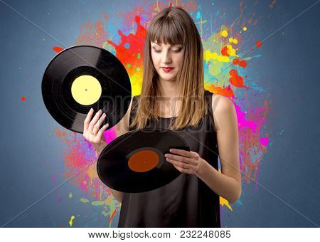 Young lady holding vinyl record on a grey background with colorful splashes behind her