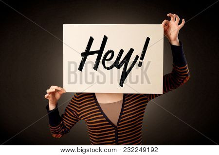 Young casual woman hiding behind a greeting drawn on paper
