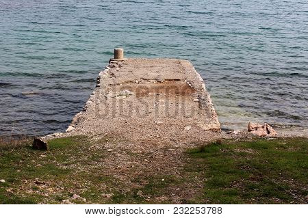 Stone Pier Surrounded With Sea With Small Waves, Uncut Grass And Small Stones On Windy Winter Day