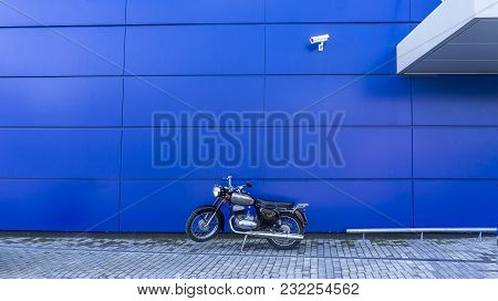 Old Motorbike Parked Against A Blue Wall Background.rocker Motor Watched By A Camera On The Wall Of
