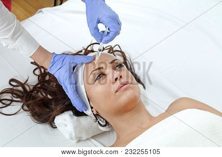 Young Woman Having Forehead Filler Injection Treatment At Beauty Clinic