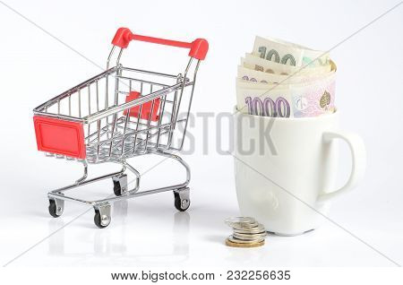 Shopping Cart And Czech Coins And Banknotes Money Currency In White Cup Symbolizing Saving Money Iso