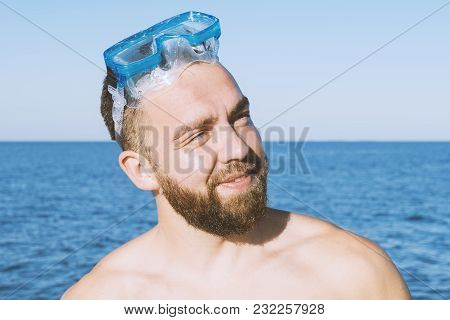 Smiling Bearded Man Suntanning On The Beach Against Blue Sea Background. Happy Vacation Concept, Sel