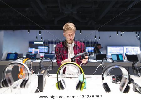 Young Man Looks At Headphones In The Electronics Store Choosing And Buying Headphones In A Technolog