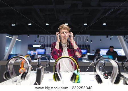 The Buyer Evaluates The Sound Of The Headphones. A Young, Handsome Man Listens To Music In A Modern