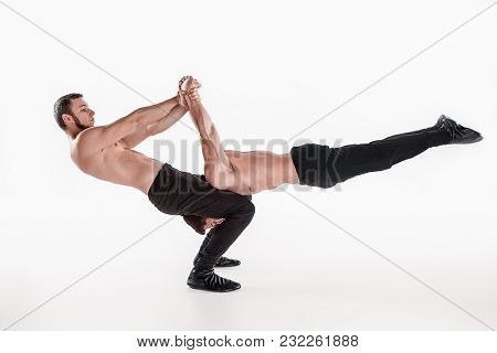 The Group Of Gymnastic Acrobatic Caucasian Men Posing In Balance Posture On White Studio Background.