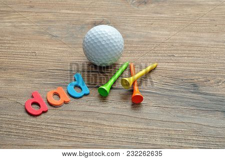 A Golf Ball With Tee's Isolated On A Wooden Background And The Word Dad