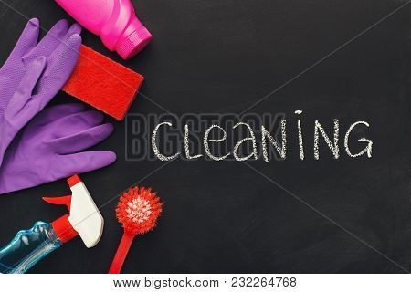 House Cleaning Products And Supplies On Black Chalk Board Background, Top View. Spring Cleaning And