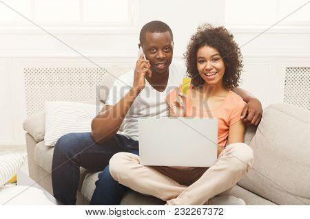 Happy Black Couple Shopping Online On Laptop, Making Order On Mobile. Freelance, Remote Work And Onl