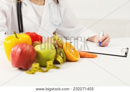 Nutritionist Desk With Healthy Fruits, Juice And Measuring Tape. Unrecognizable Dietitian Working On