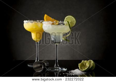 Classic Lime Margarita And Orange Margarita Cocktail Mix In Salt Rimmed Glasses Garnished With Slice