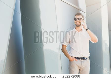 Attractive Happy Businessman Or Lawyer In Sunglasses Is Talking On Cell Phone And Putting His Hand I