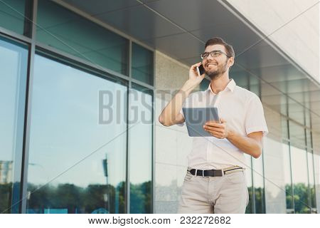 Handsome Happy Businessman Is Making A Phone Call And Holding Digital Tablet While Standing Near Mod