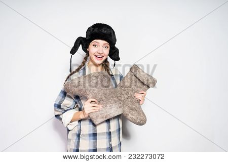 Happy Young Russian Girl In Warm Fur Hat Holds Winter Felt Boots In Hands, Smiling