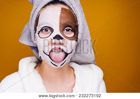 Funny Young Girl With A Towel On Her Head Showing Tongue, On Face Mask With A Picture Of Muzzle Of A