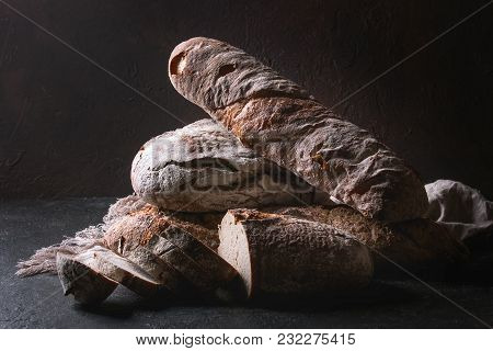 Variety Of Loafs Fresh Baked Artisan Rye And Whole Grain Bread On Linen Cloth Over Dark Brown Textur