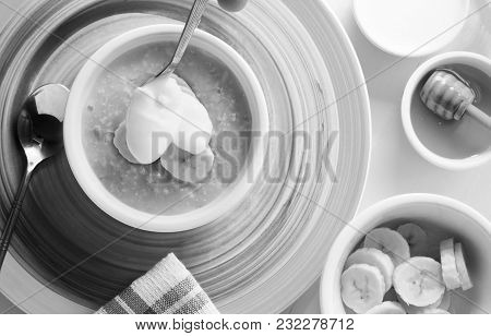 A Breakfast Table Of Organic Hot Porridge And Banana With Honey. Black And White