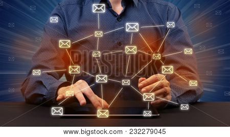 Businessman in suit typing with connected mail icons around