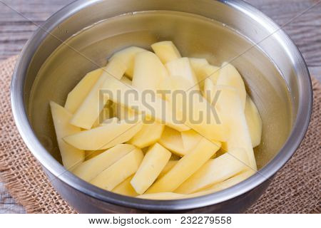 Sliced Potatoes In Water In A Metal Bowl Before Cooking