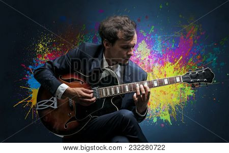 Young classical guitarist musician with colorful splotch wallpaper