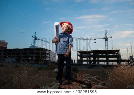 Cute Caucasian Little Boy In Helmet With Paper Of Draft In His Hand On Construction Site With Crane
