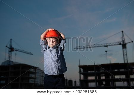 Boy Blows His Cheeks Clutching His Head In Helmet Against Background Of Building Cranes And Construc
