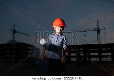 Sad Little Boy Builder In Orange Helmet With Tool Box And Paper Plan On Construction Site Background