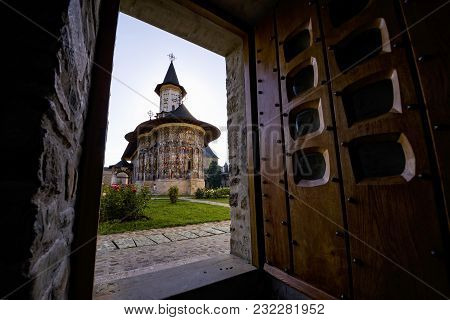 Painted Church Monastery Of Bucovina Region In Romania Seen Through A Doorway