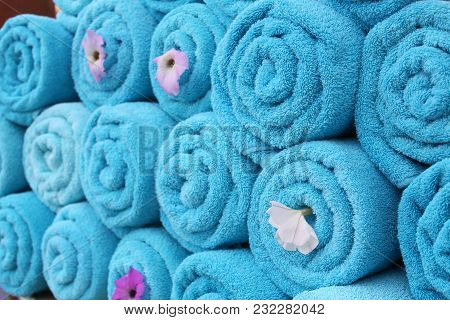 Blue Roll Towels. Clean Fresh Towels With Fresh Flowers Neatly Stacked On Top Of Each Other. Spa. Ma