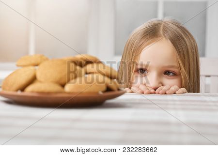 Hungry Girl With Blonde Straight Hair And Big Brown Eyes Is Looking On Delicious Cookies On White Ta