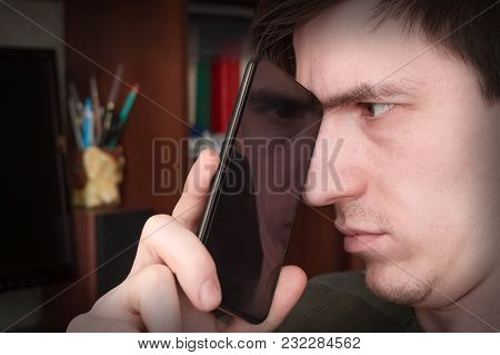 Guy Looks At The Screen Of A Smartphone, Through The Reflection Of The Screen Looks One Eye Into The
