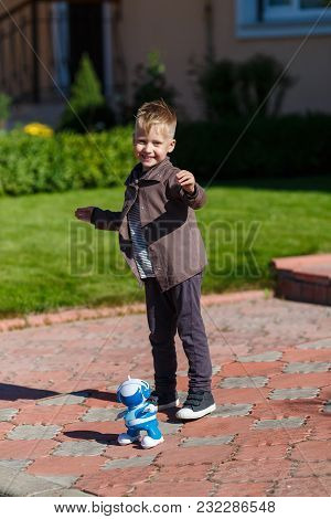 Little Blond Boy Playing With Robot At The Yard, Outdoor. Kid Having Fun And Dancing With Mechanical