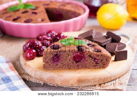 A Piece Of Chocolate Pie With A Cherry On A Wooden Table