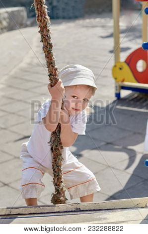 Portrait Of Funny Little Boy Playing And Climbing With Rope On Summer Day