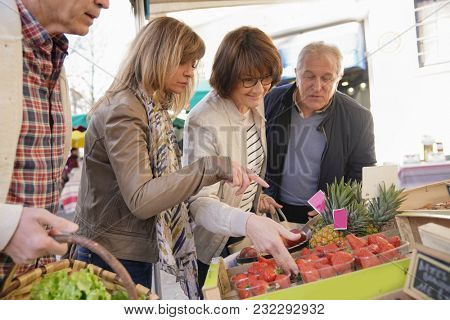 Senior people buying strawberries at the farmer's fresh market
