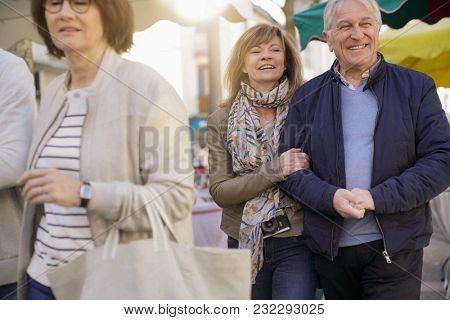Senior couple on vacation walking in green outdoor market