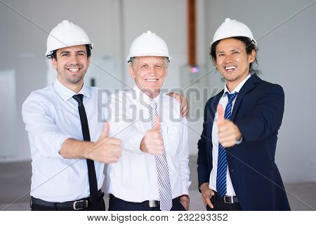 Pleased Friendly Multiethnic Architects Showing Thumb Ups As Symbol Of Good Job. Cheerful Successful