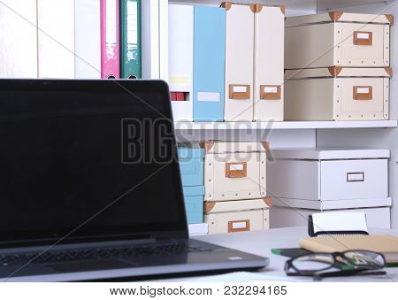 Close-up Of Comfortable Working Place In Office With Laptop, Mouse, Notebook, Glasses, Pen And Other
