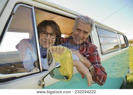Portrait of cheerful senior couple sitting in vintage camper van