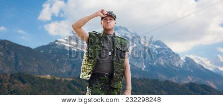 army, national service and people concept - young soldier or ranger wearing military uniform over mountains background