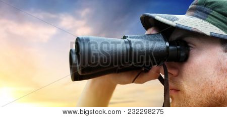 army, military service and people concept - close up of young soldier, ranger or hunter with binocular looking at something over sky background