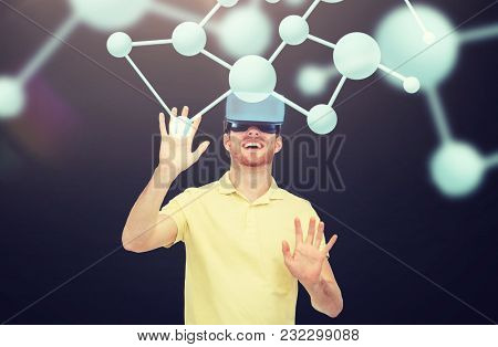 3d technology, virtual reality, science, biology and people concept - happy young man with virtual reality headset or 3d glasses playing game over black background and molecules