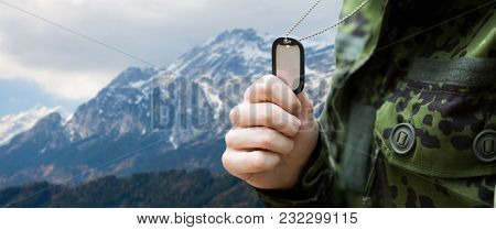 army, national service and people concept - close up of young soldier military badge over mountains background